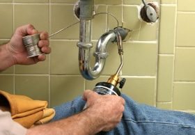 Showing a plumbing contractor working on repairing a sink pipe